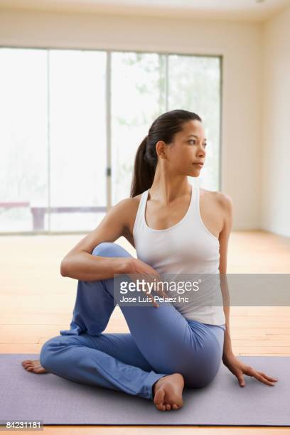 mixed race woman doing yoga - twisted stock pictures, royalty-free photos & images