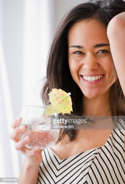 Mixed race woman drinking cocktail