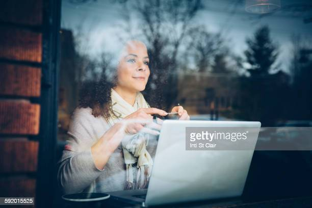 Mixed race woman drinking coffee and using laptop in cafe