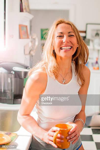 Mixed race woman drinking coffee in kitchen