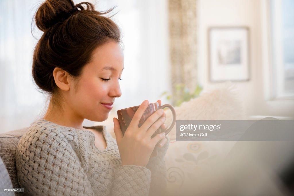 Mixed race woman drinking coffee on sofa : Foto de stock