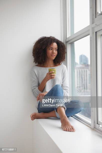 Mixed Race woman drinking coffee on window sill