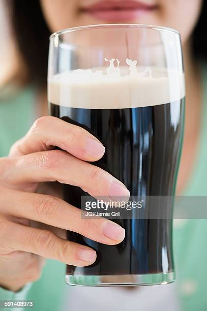Mixed race woman drinking glass of dark beer