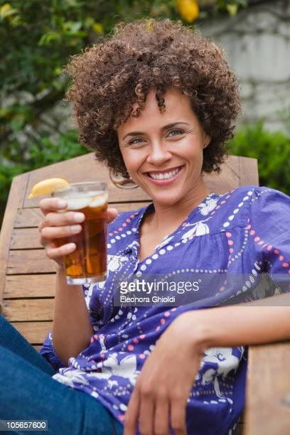 Mixed race woman drinking iced tea