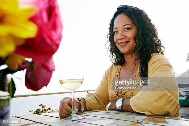 mixed race woman drinking wine at waterfront - donna creola foto e immagini stock