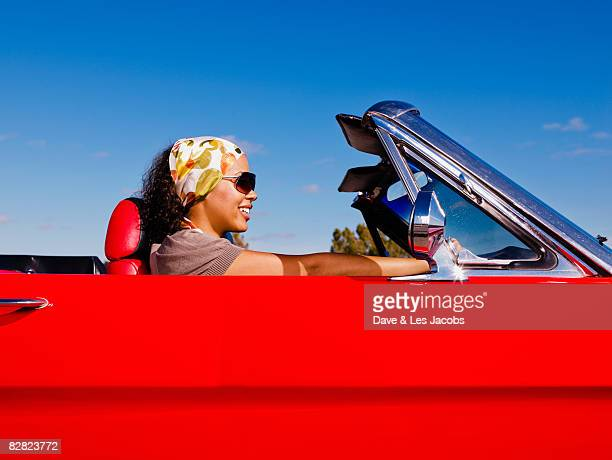 Mixed race woman driving red convertible