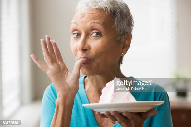 Mixed race woman eating cake