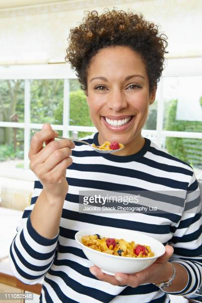 Mixed race woman eating cereal