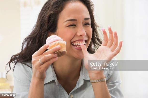 mixed race woman eating cupcake - messa a fuoco differenziale foto e immagini stock