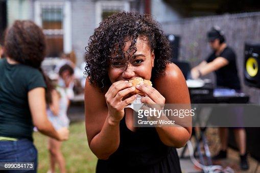 Mixed Race woman eating hamburger at backyard party