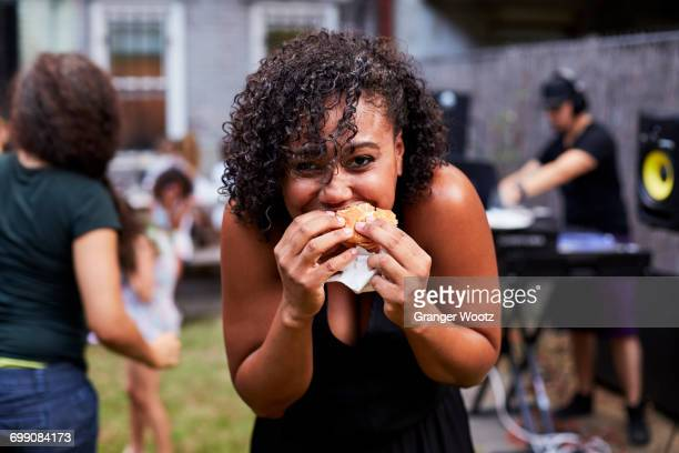 mixed race woman eating hamburger at backyard party - biting stock pictures, royalty-free photos & images