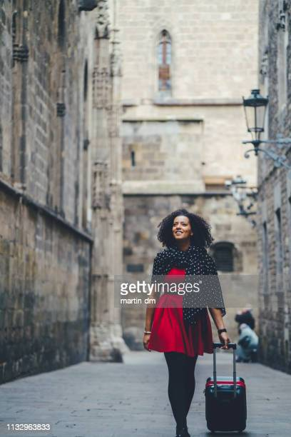 mixed race woman enjoying barcelona - wheeled luggage stock photos and pictures