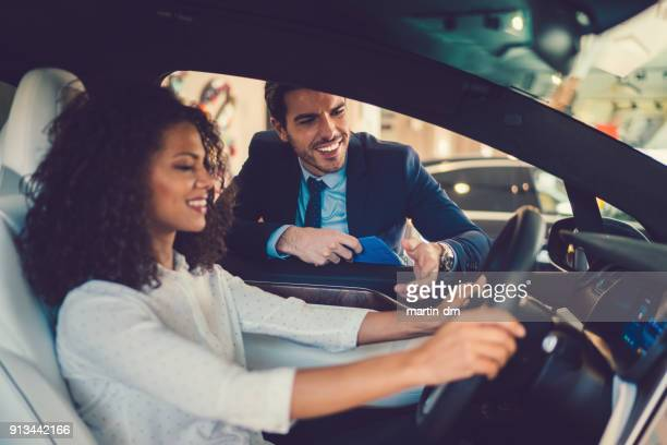 mixed race woman enjoying new car - showroom stock pictures, royalty-free photos & images