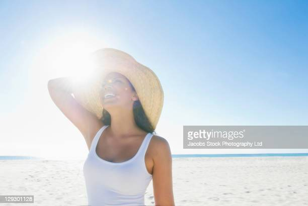 mixed race woman enjoying the sun at the beach - sun hat stock pictures, royalty-free photos & images