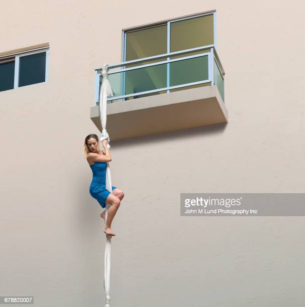 mixed race woman escaping balcony on knotted sheets - escaping stock pictures, royalty-free photos & images