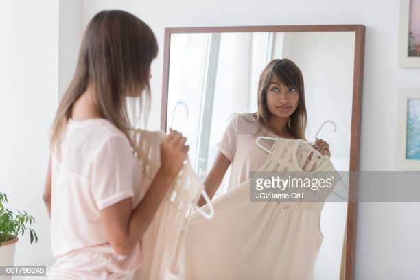 Mixed race woman examining dress in mirror