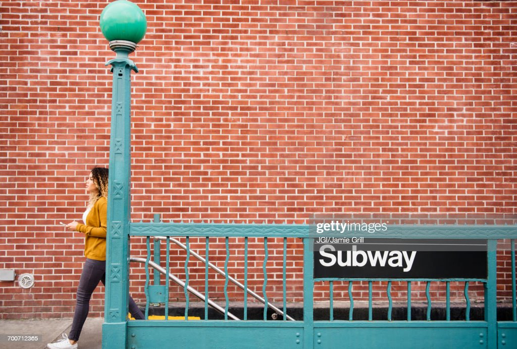 Mixed Race woman exiting subway station in city : Foto de stock