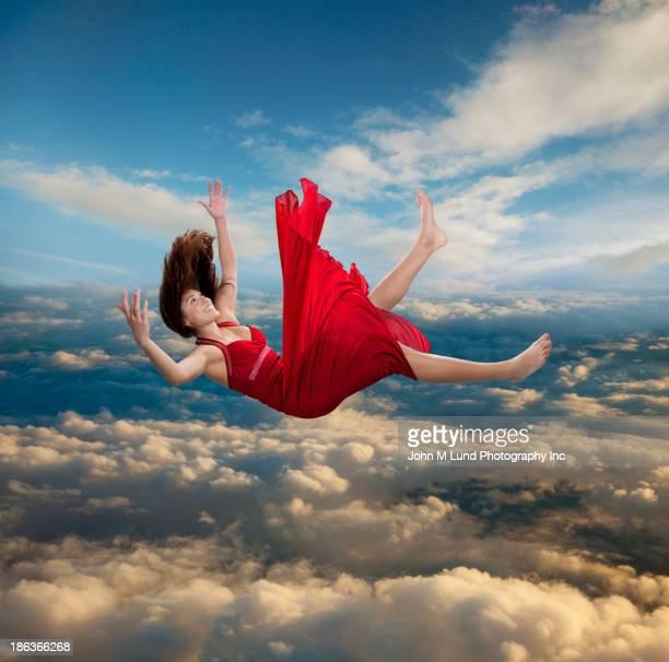 Mixed race woman falling through clouds