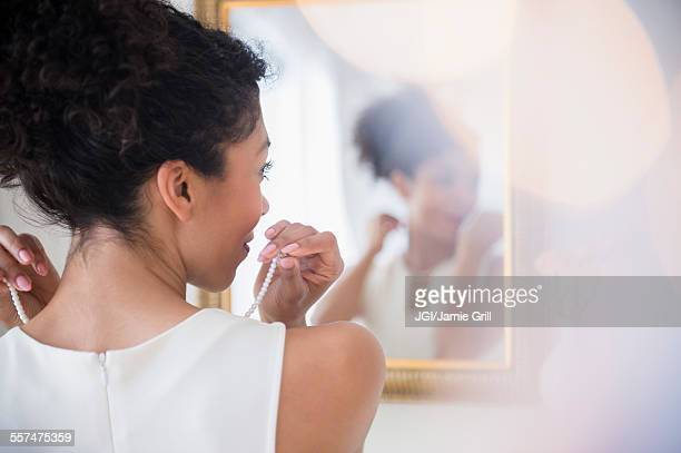 mixed race woman fastening pearl necklace in mirror - collar fotografías e imágenes de stock
