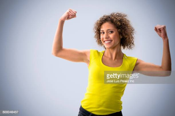 mixed race woman flexing her muscles - flexing muscles stock pictures, royalty-free photos & images