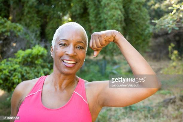 mixed race woman flexing muscles outdoors - flexing muscles stock pictures, royalty-free photos & images