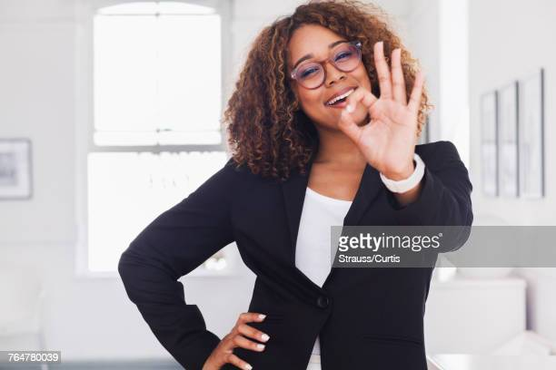 Mixed race woman gesturing okay in gallery