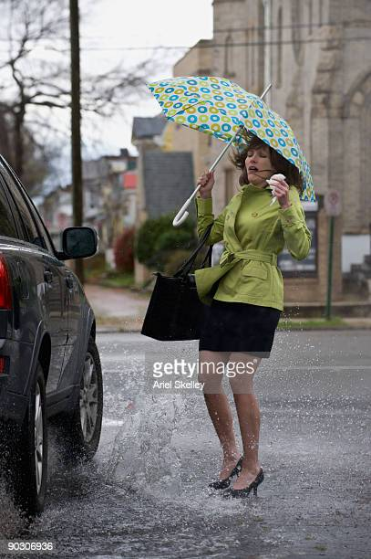 mixed race woman getting splashed by car - nass stock-fotos und bilder