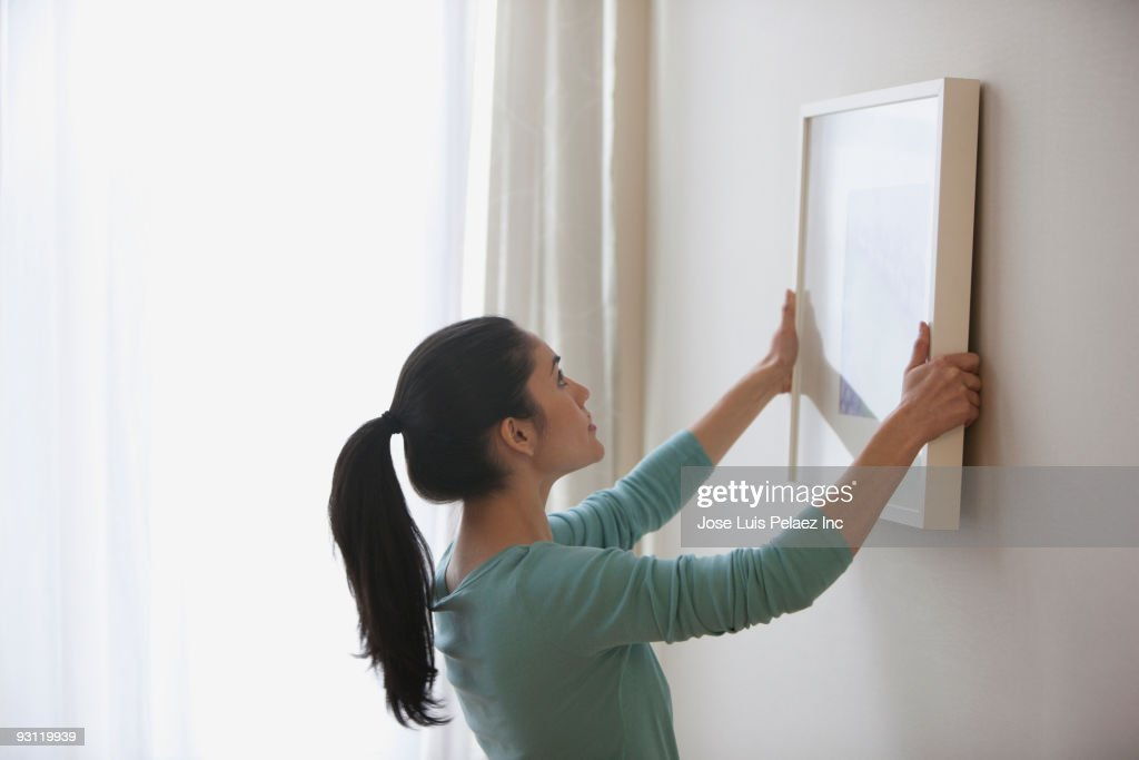 Mixed race woman hanging picture on wall : Stock Photo