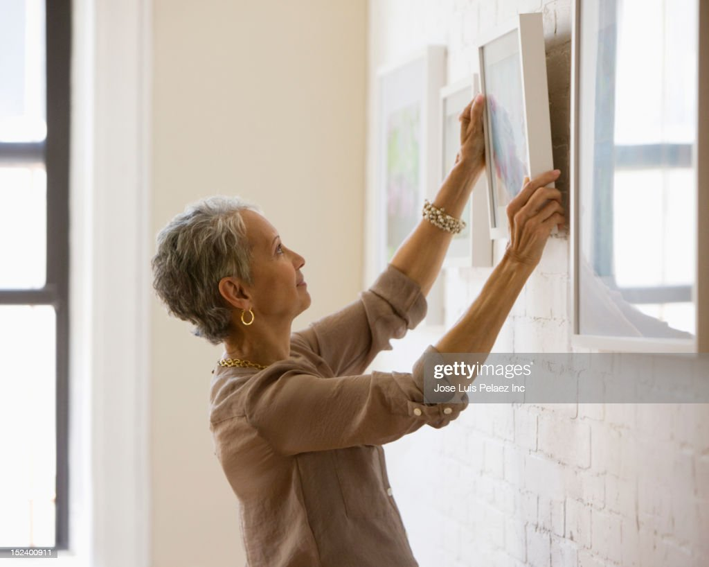 Mixed race woman hanging pictures on wall : Stock Photo