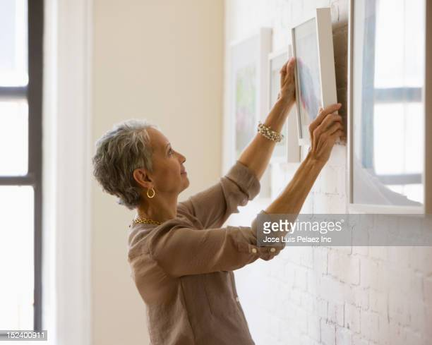 mixed race woman hanging pictures on wall - galleria d'arte foto e immagini stock