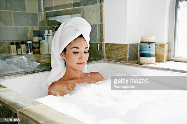 mixed race woman having bubble bath - bubble bath stock pictures, royalty-free photos & images