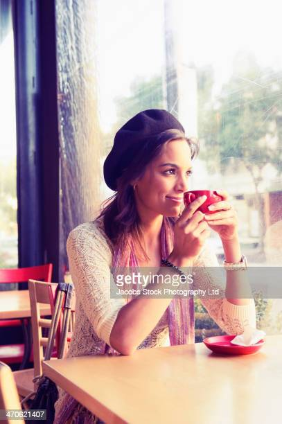Mixed race woman having coffee in cafe