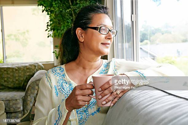 mixed race woman having cup of coffee on sofa - asian 50 to 55 years old woman stock photos and pictures
