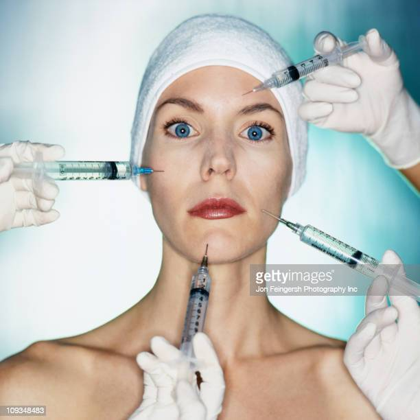 Mixed race woman having facial injections