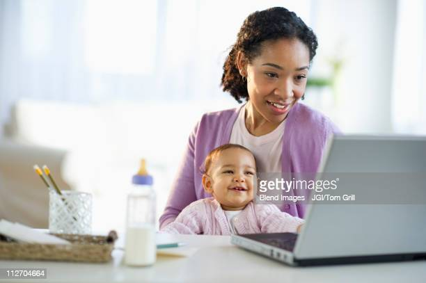 Mixed race woman holding baby and using laptop