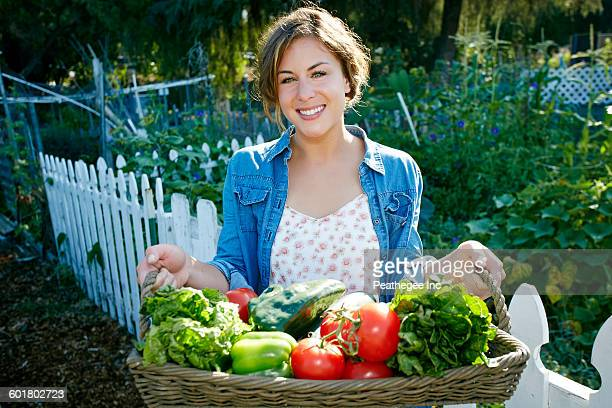 Mixed race woman holding basket of vegetables in garden