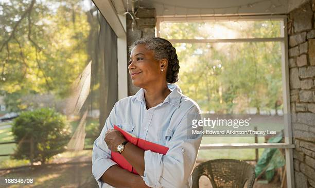 Mixed race woman holding book on porch