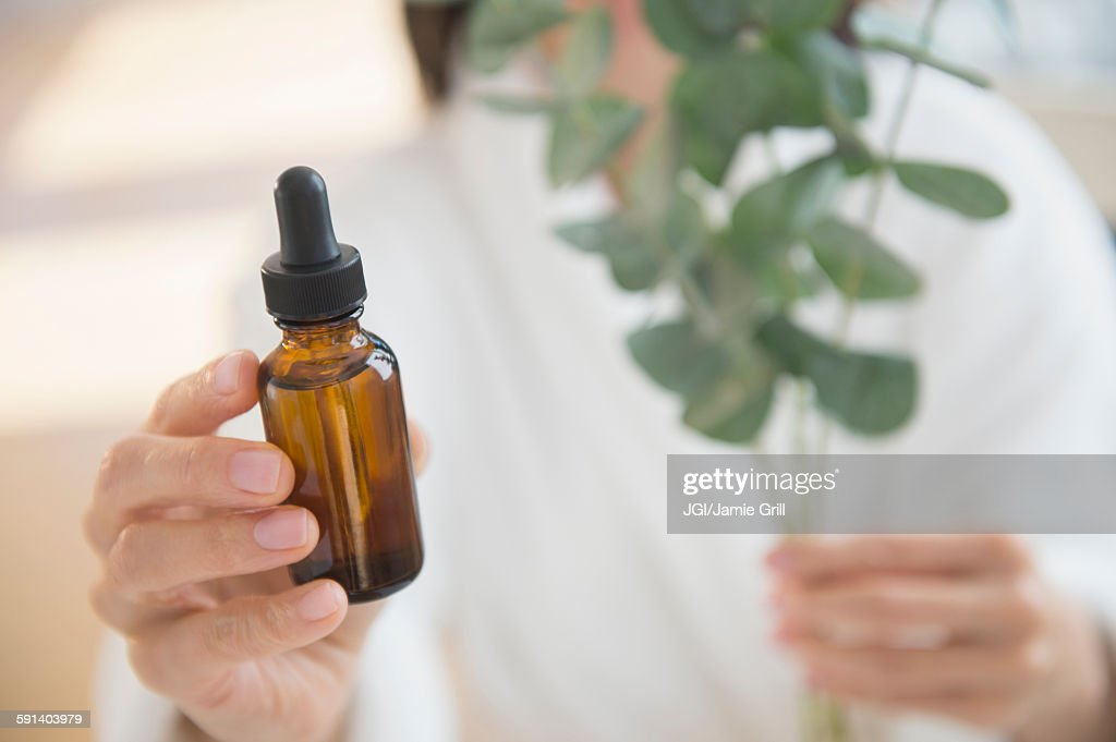 Mixed race woman holding bottle of essential oil : Stock Photo