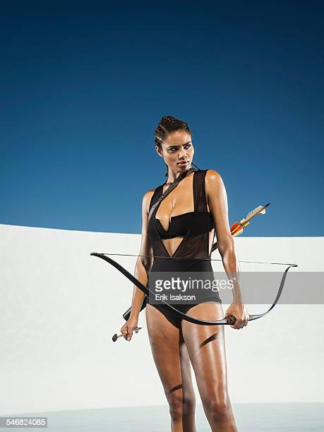 Mixed race woman holding bow and arrow