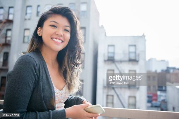 mixed race woman holding cell phone in city - williamsburg new york city stock pictures, royalty-free photos & images