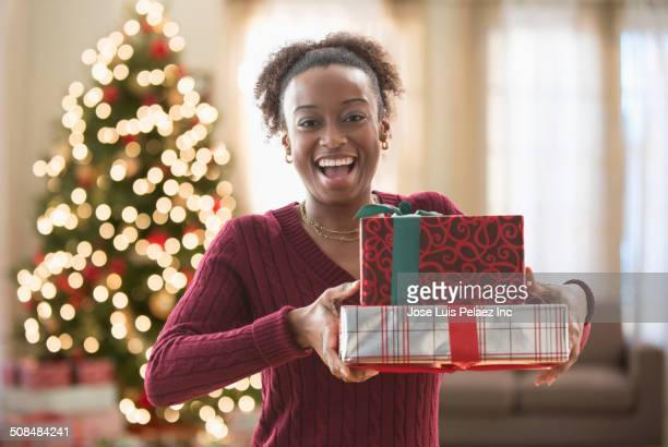 Mixed race woman holding Christmas gifts
