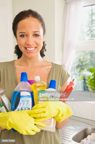 Mixed race woman holding cleaning products in kitchen
