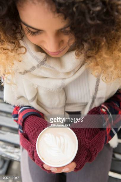 mixed race woman holding coffee cup with leaf in foam - mitten stock pictures, royalty-free photos & images