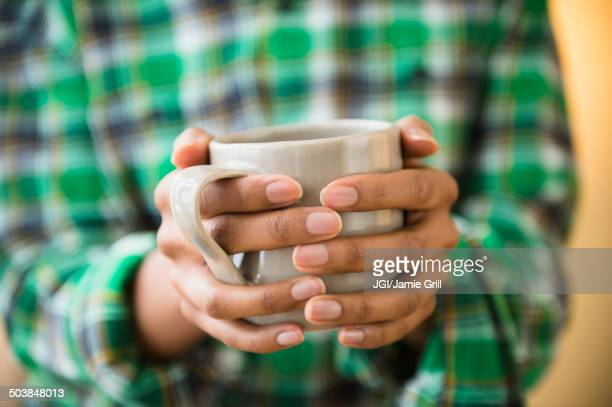 Mixed race woman holding cup of coffee