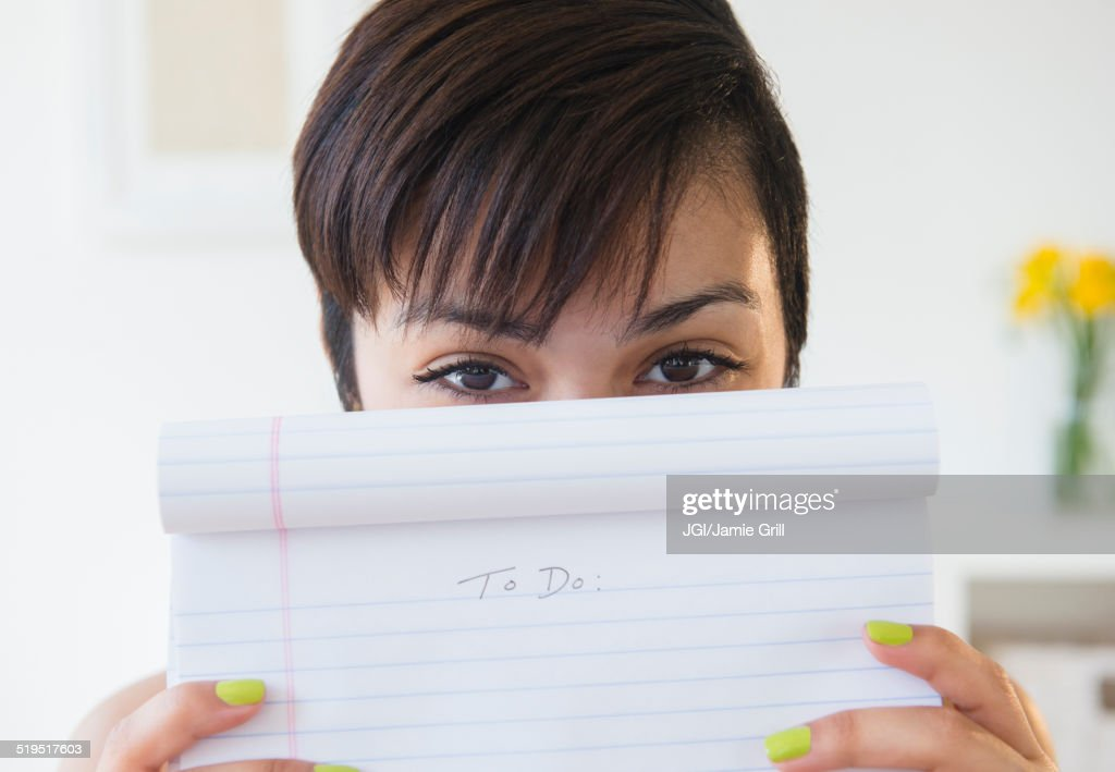 Mixed race woman holding empty to do list : Stock Photo