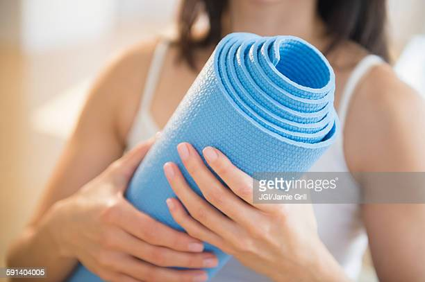 mixed race woman holding exercise mat - mat stock pictures, royalty-free photos & images