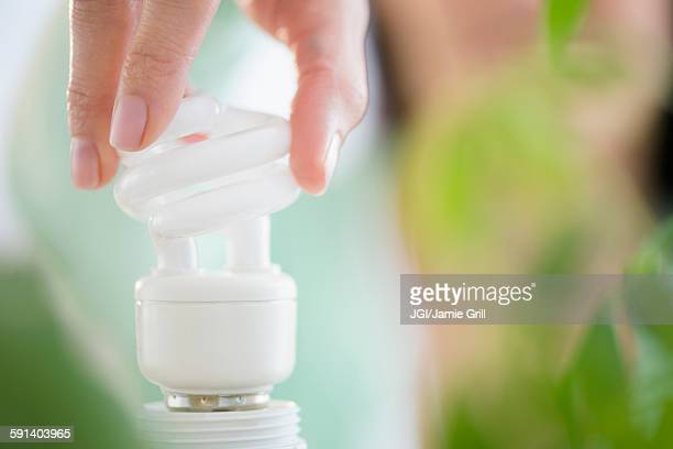 Mixed race woman holding fluorescent light bulb