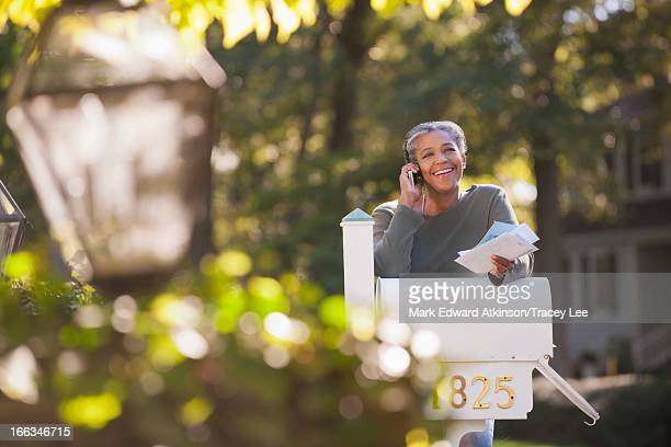 mixed race woman holding mail and talking on cell phone - cherokee indian women stock pictures, royalty-free photos & images
