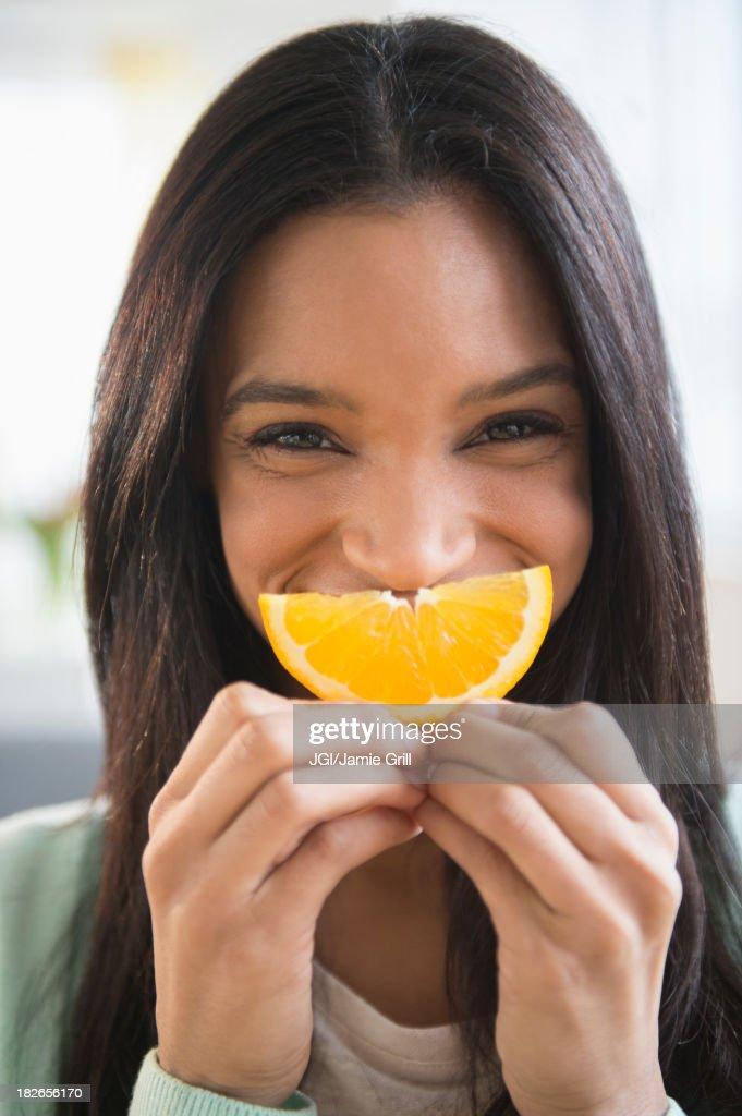 Mixed race woman holding orange slice : Stock Photo