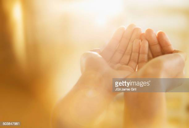 mixed race woman holding out cupped hands - praying stock pictures, royalty-free photos & images